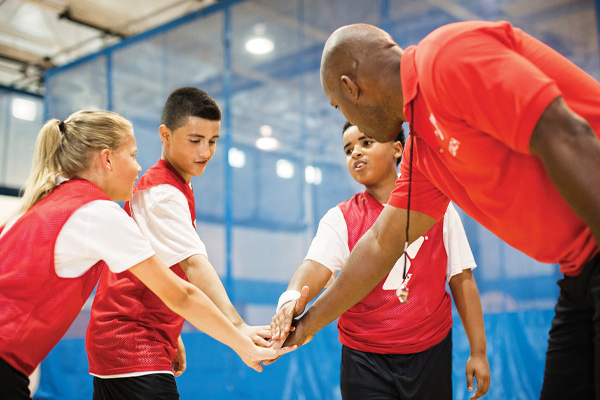 Coach with kids on the basketball court