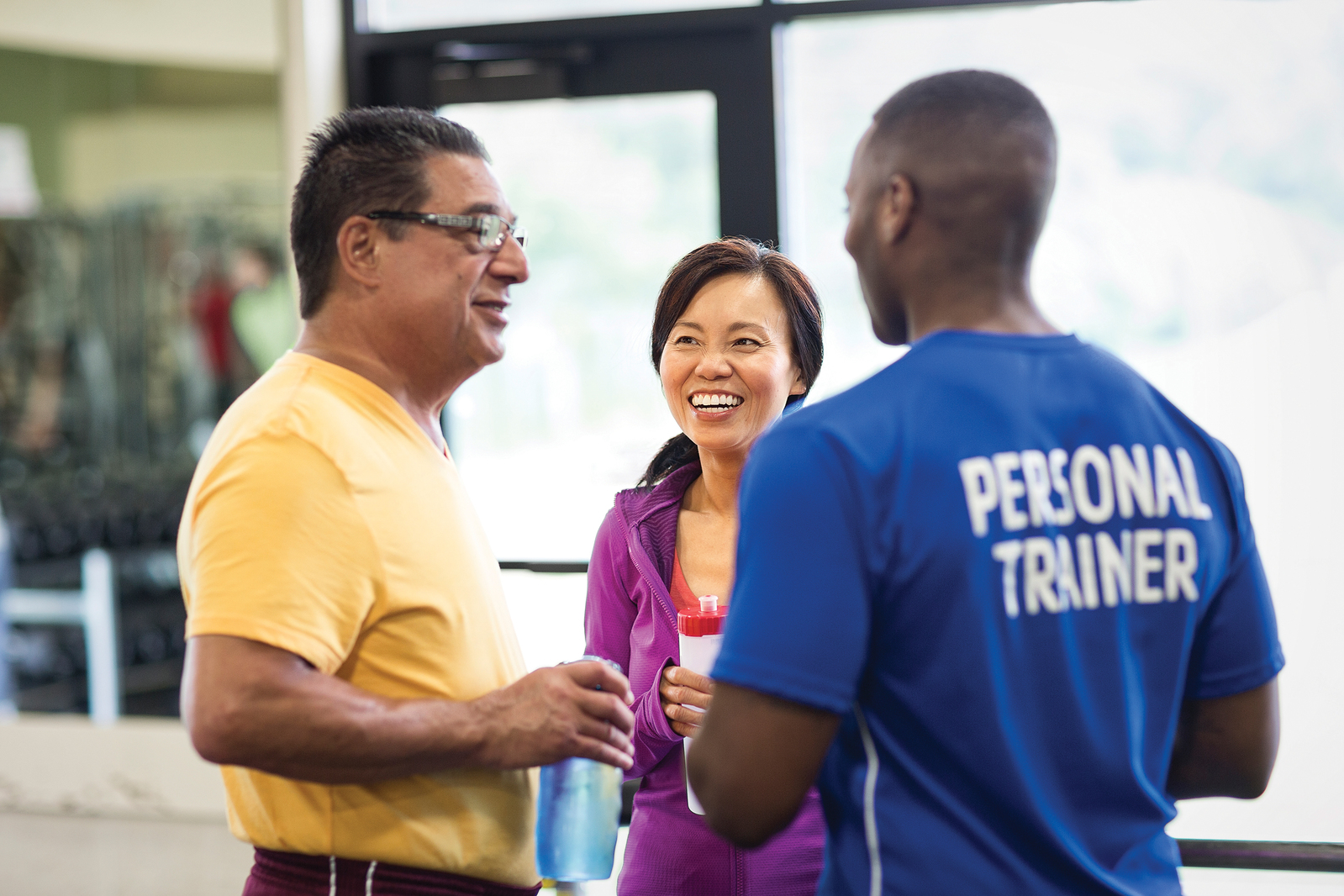 Male personal trainer speaking with 2 potential clients