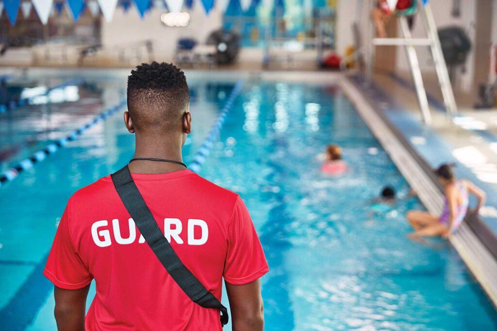 Lifeguard, standing facing pool