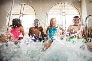 Kids sitting on side of pool splashing with their feet