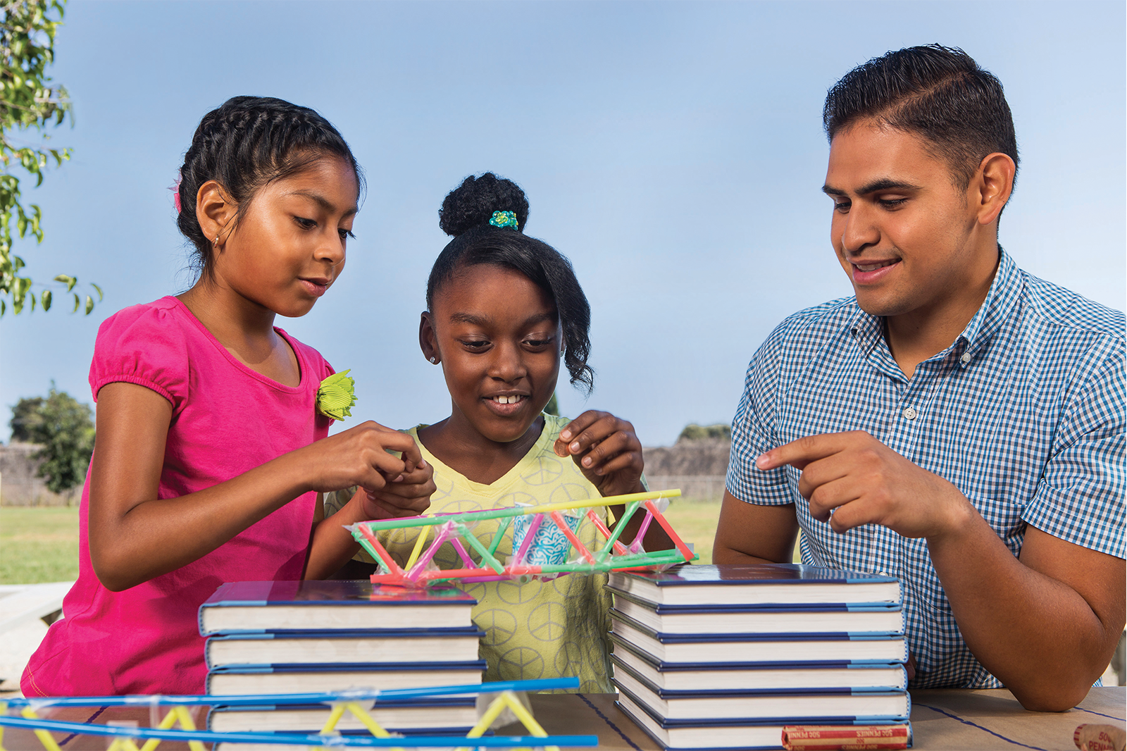an adult assisting 2 young ladies to build a straw bridge