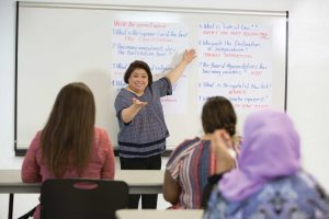 Woman pointing to a whiteboard in front of a classroom