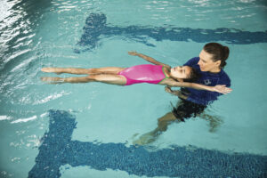 Female swim instructor teaching young girl how to swim