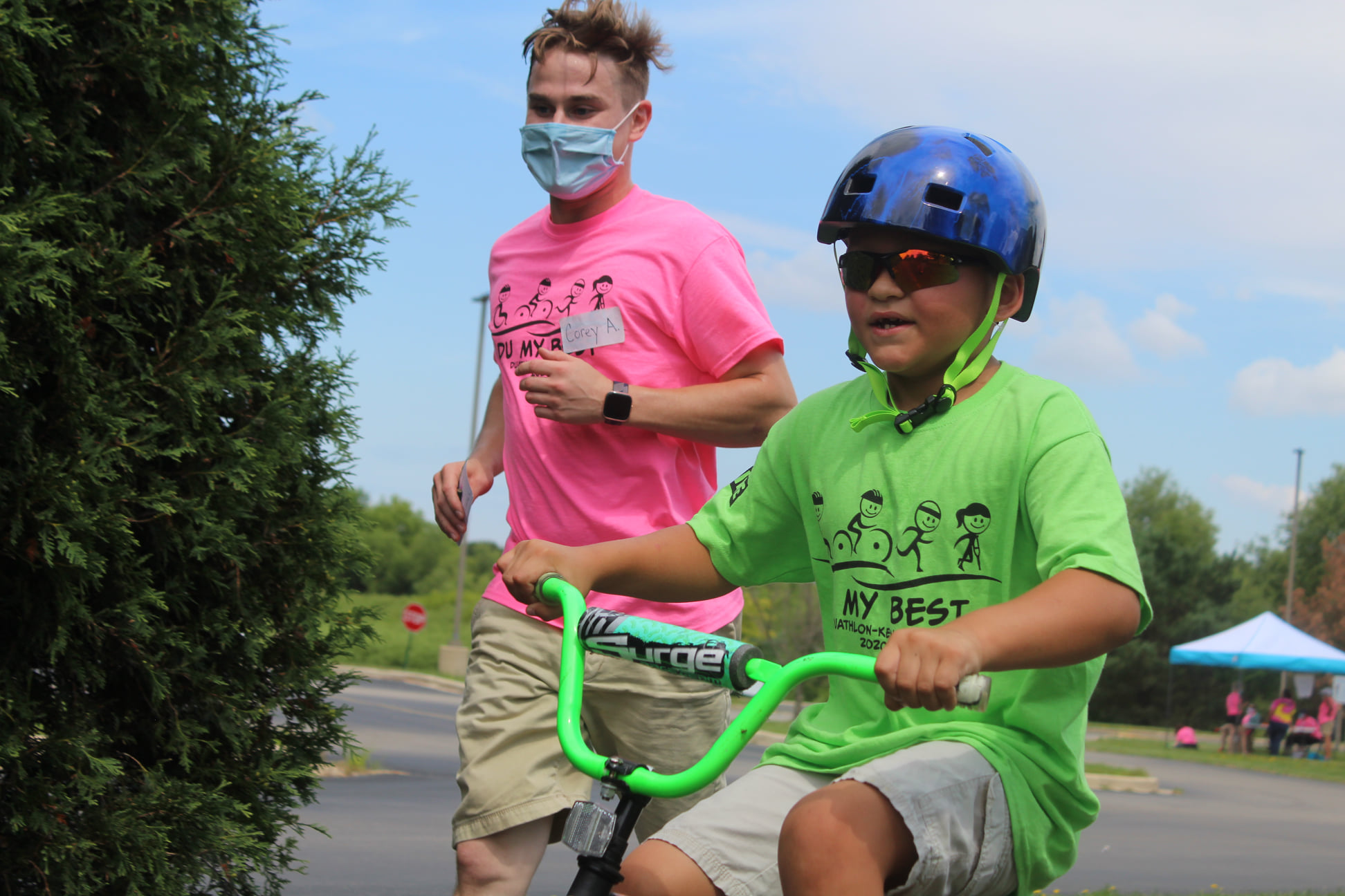 Volunteer running next to a young boy on bike
