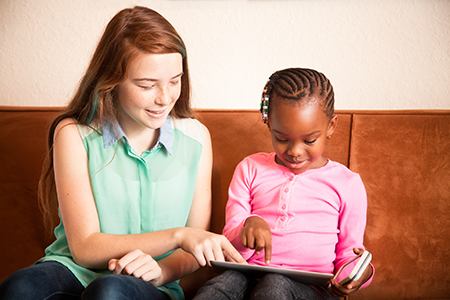 Teenager reading to young child